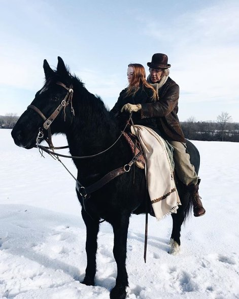 Amybeth McNulty riding in a horse with her co-actor