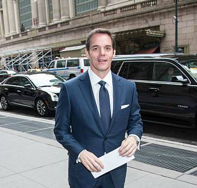 Bill Hemmer doing reporting standing in front of cars