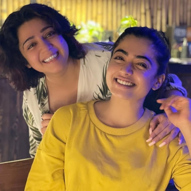 Charmy Kaur posing from behind Rashmika Mandanna as they both smile for the camera