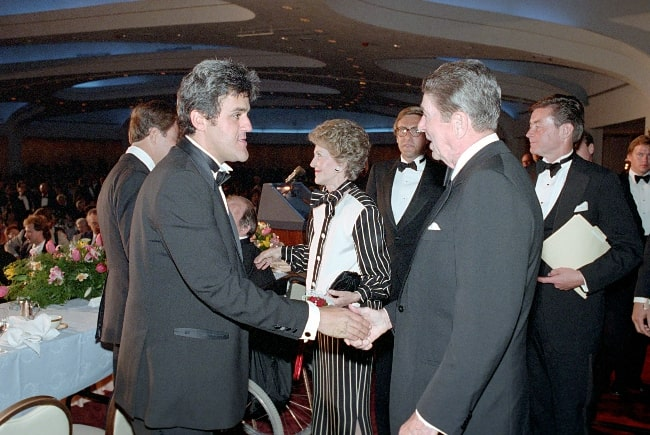 Jay Leno (Left) and President Ronald Reagan pictured while shaking hands at The White House Correspondents Association Dinner at The Hilton Hotel in Washington DC